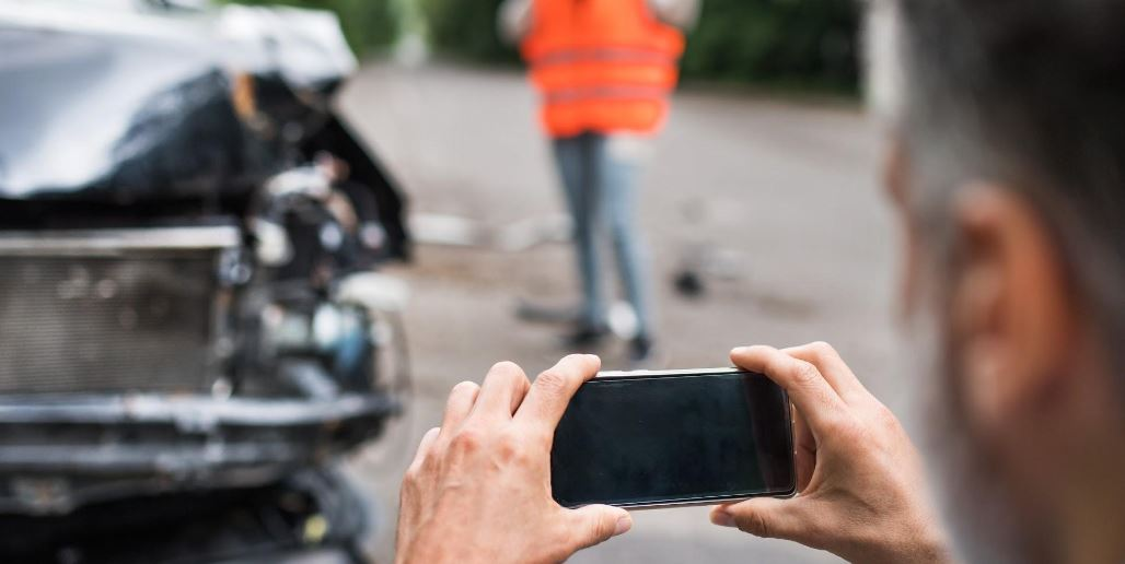 Man taks a picture of the car accident