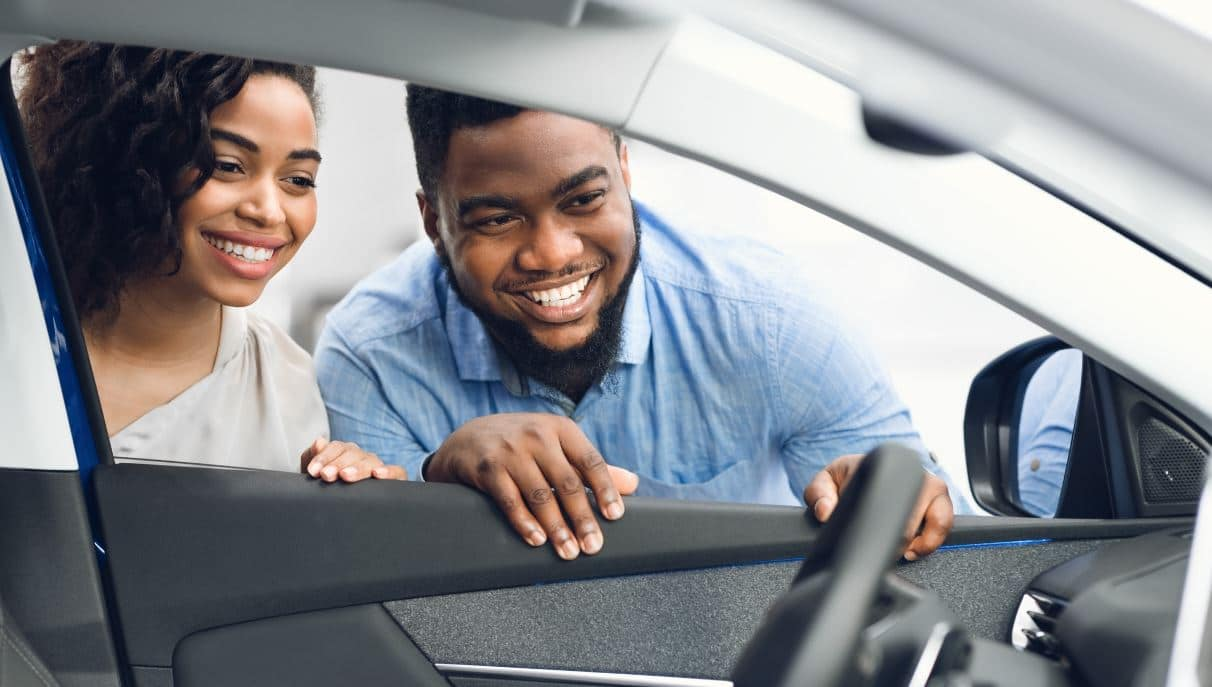 A couple checking the interior of a new car